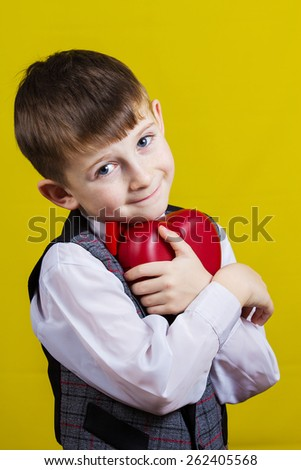 Happy, smiling little boy holding Red heart isolated on yellow background.Concept Love,Care,Health.Facial expression.