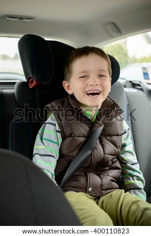 Happy smiling little boy in car safety seat. Children car safety concept