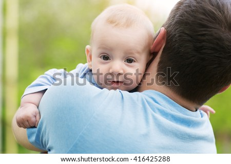Happy smiling little boy in his father's hands wearing blue clothes - stock photo