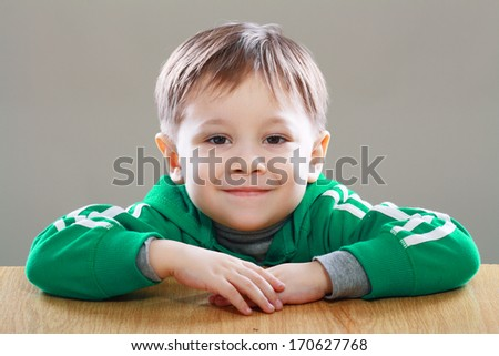 Happy Smiling little boy sits at the desk isolated on grey background