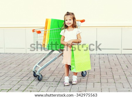 Happy smiling little girl child and trolley cart with colorful shopping bags in city