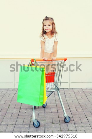 Happy smiling little girl child sitting in trolley cart with colorful shopping bags having fun - stock photo