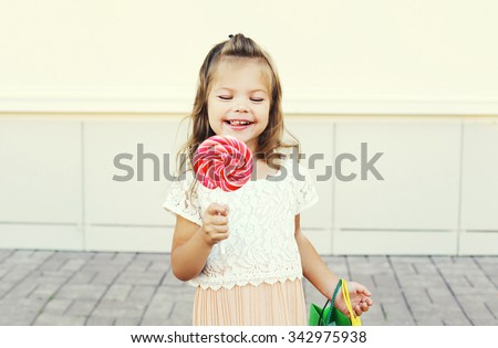 Happy smiling little girl child with sweet caramel lollipop having fun in city  - stock photo