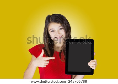 Happy smiling little girl holding tablet, and pointing to it with two hands  over yellow background.