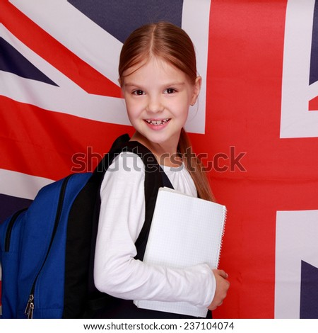 Happy smiling little girl in a school uniform stands on a background of the flag of Great Britain/British school girl on background of the flag of England - stock photo