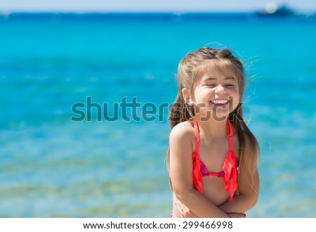 Happy smiling little girl on beach vacation, blue and clear sea background - stock photo