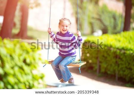 happy smiling little girl on swing - stock photo