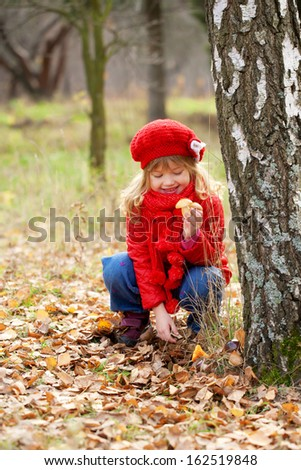 Happy smiling little girl picking mushrooms. Fall concept.