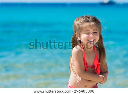 Happy smiling little girl playing at sea, tropical sea background. - stock photo