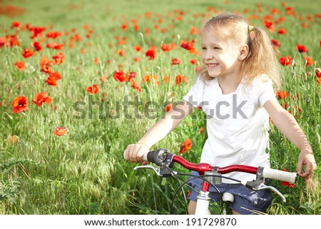 Happy smiling little girl standing with bicycle on the poppy meadow laughing looking away - stock photo
