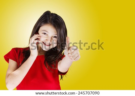 Happy Smiling Little Girl talking on the mobile phone and gesturing making thumb up while standing isolated on white.Success,Communications, - stock photo
