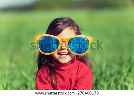 Happy smiling little girl wearing big sunglasses in the field - stock photo