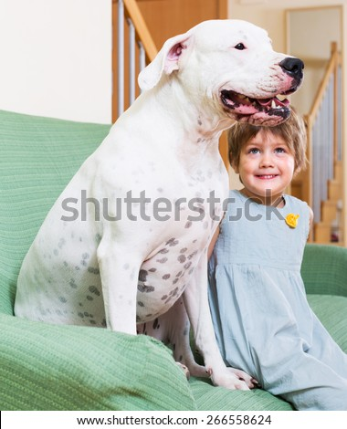 Happy smiling little girl with big white dog at home. Focus on dog - stock photo