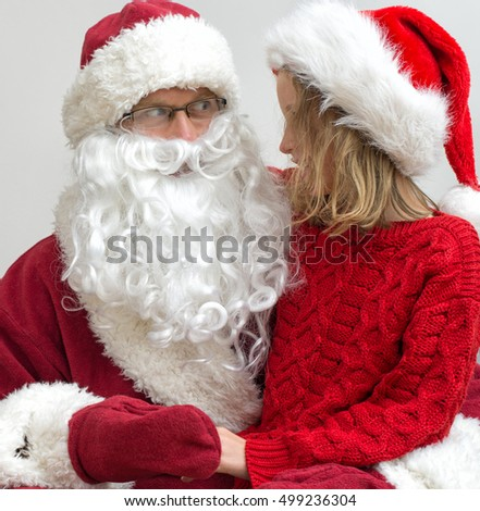 Happy smiling little girl with Santa Claus.