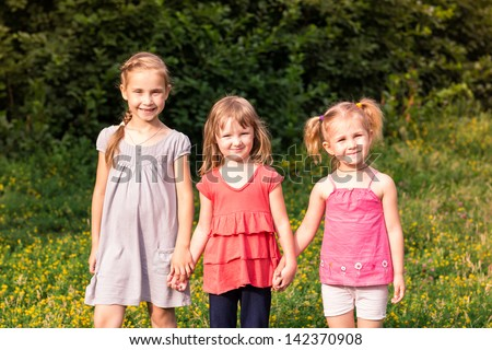Happy smiling little kids outdoor in the park in summertime - stock photo