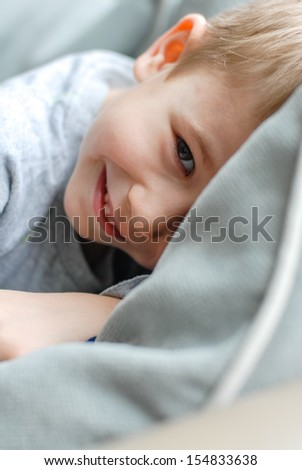 happy smiling & looking at camera kid hiding in bedroom at home - stock photo