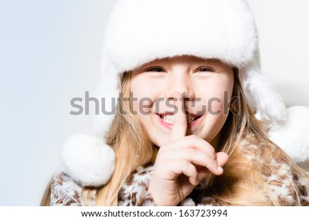 happy smiling & looking at camera little girl secrets in white winter hat - stock photo