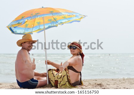 happy smiling & looking at camera mature couple sitting at seashore on summer sandy beach outdoors background - stock photo