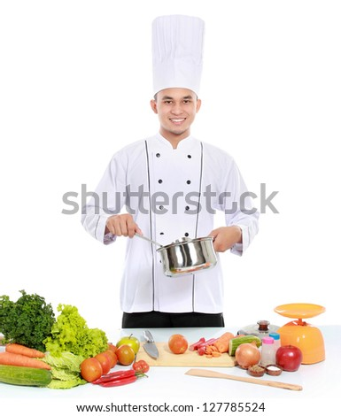 happy smiling male chef cooking in the kitchen - stock photo