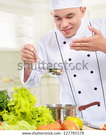 happy smiling male chef smell his cooking in the kitchen - stock photo