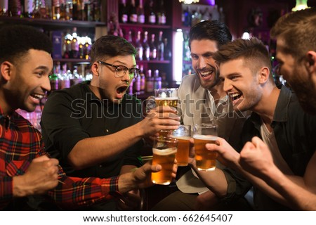 Happy smiling male friends clinking with beer mugs in pub