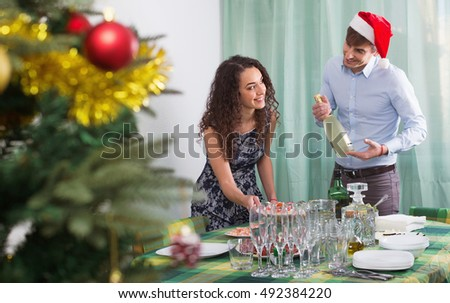 Happy smiling man and girl serving Christmas table for  guests in home