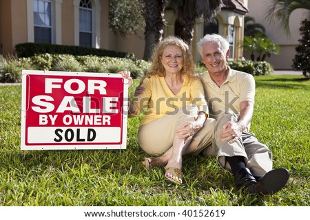 Happy, smiling man and woman senior couple sitting on the grass outside their home with For Sale Sold by owner sign.