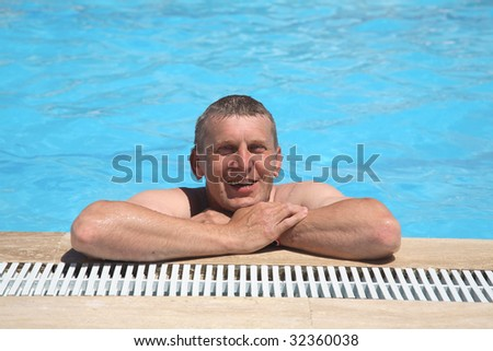 happy smiling man bathes in pool - stock photo