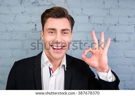"Happy smiling man in black jacket gesturing ""OK"" - stock photo"