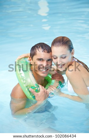 Happy smiling man learning to swim with floating ring in swimming pool - stock photo
