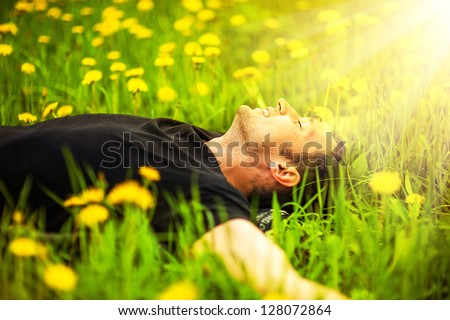 Happy smiling man lying on grass with yellow dandelion at sunny day - stock photo