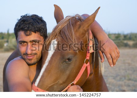happy smiling man petting his horse