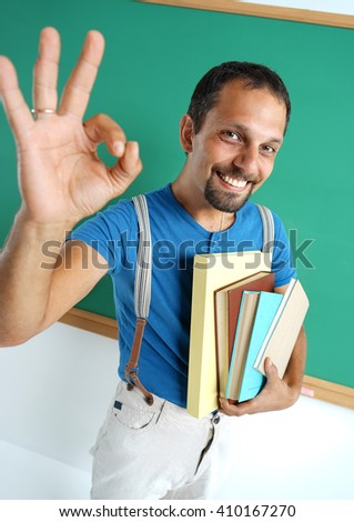 Happy smiling man showing okay gesture. Photo of smiling adult student, creative concept with Back to school theme - stock photo