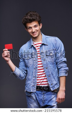 Happy smiling man wearing denim jacket showing showing blank paper card sign with copy space for text, over gray background - stock photo