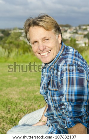 happy smiling mature man in forties sitting in a park and wearing a blue checked shirt.