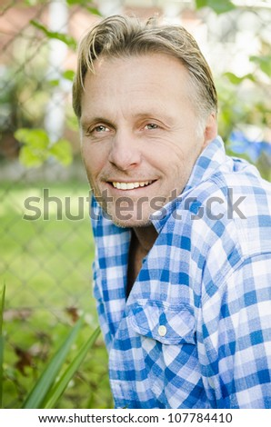 happy smiling mature man in forties wearing blue checked shirt. - stock photo