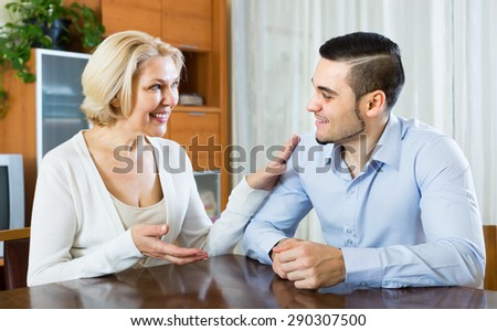 Happy smiling mature woman chatting with young boyfriend indoors