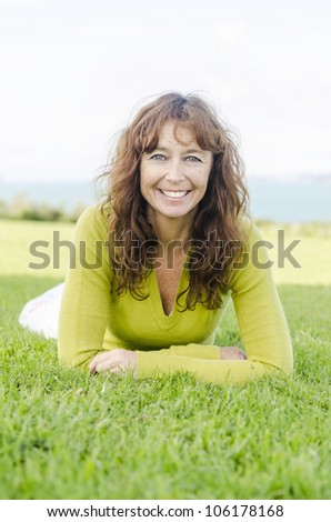happy smiling mature woman laying on the grass - stock photo