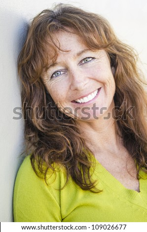 happy smiling mature woman with long auburn hair and freckles wearing a lime green jumper.
