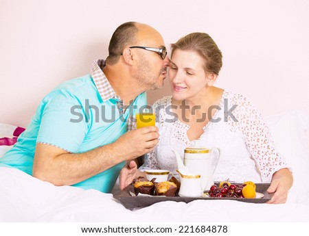 Happy, smiling middle aged couple enjoying one another while having breakfast in bed, vacation times, in hotel, house bedroom. Human emotion face expression feeling, relationship concept - stock photo