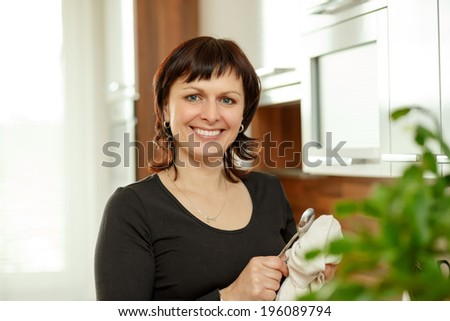 happy smiling middle-aged woman wipes the dishes in the kitchen - stock photo