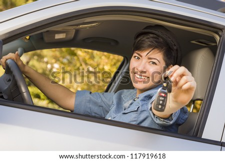 Happy Smiling Mixed Race Woman in Car Holding Set of Keys. - stock photo