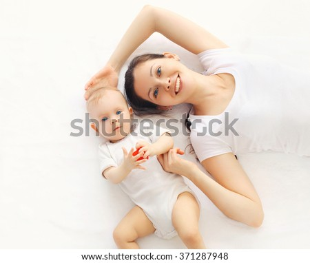 Happy smiling mother and baby lying on bed at home, top view - stock photo