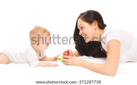 Happy smiling mother and baby playing in toys over white background - stock photo