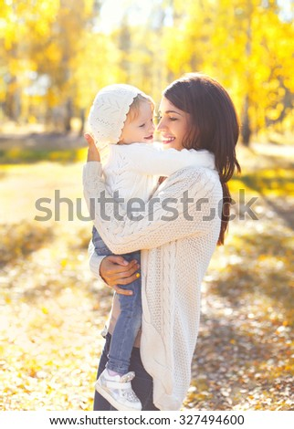 Happy smiling mother and child playing having fun in sunny warm autumn day - stock photo