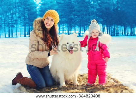 Happy smiling mother and child with white Samoyed dog together in winter - stock photo