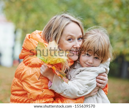 Happy smiling mother and daughter in autumn leaves park - stock photo