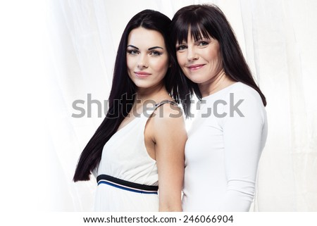 Happy smiling mother and daughter on white background - stock photo