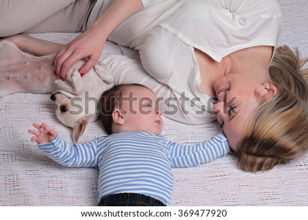 Happy smiling Mother and 3 month old baby boy and dog enjoying at home - stock photo