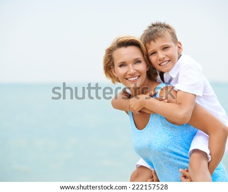 Happy smiling mother and son having fun on the beach.
